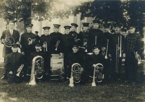 A black and white photograph of a brass band in uniforms with hats standing under trees in a park; front row kneeling; all fifteen members hold an instrument