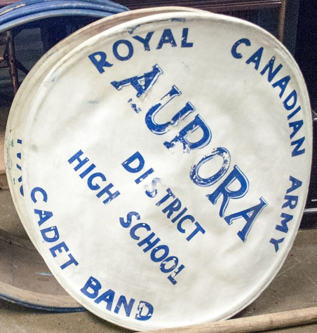The skin of a drum dislodged from the drum body with painted blue lettering