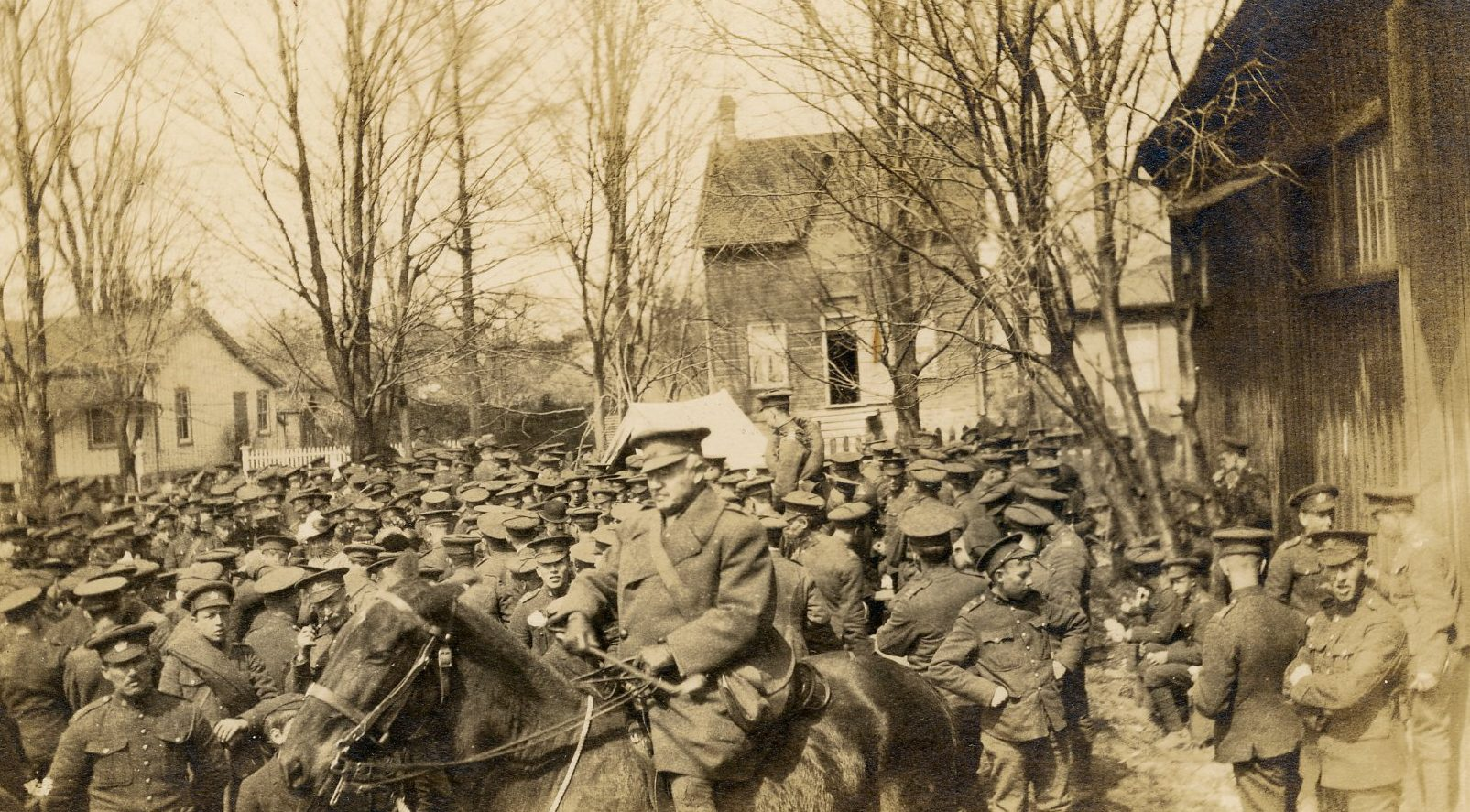A black and white photograph of a large group of soldiers standing to the left of a wooden building; a mounted officer is in the foreground; trees and houses in the background