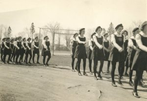 A black and white photograph depicting a line of girl cadets in uniform marching through a park; baseball diamond and houses visible in background