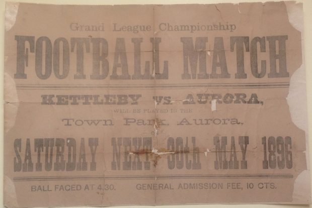 A horizontally oriented paper poster with a brown background and soft text advertising a football match in Town Park. The poster is significantly ripped along the two side edges as well as the top edge.
