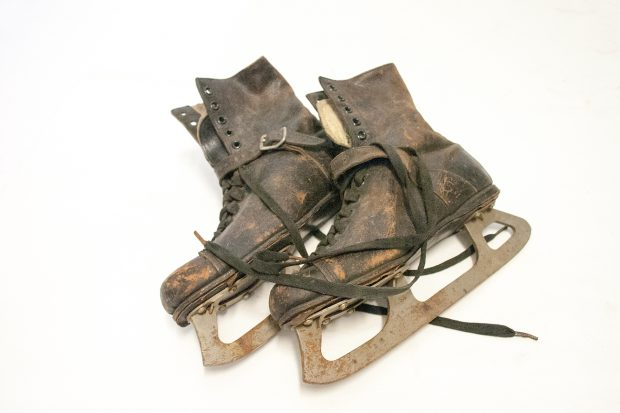 Pair of ice skates, complete with boots; boots dark brown leather with lace and eyelet fastening, and strap over front of ankle, fleecy lining; steel blade shows signs of rust