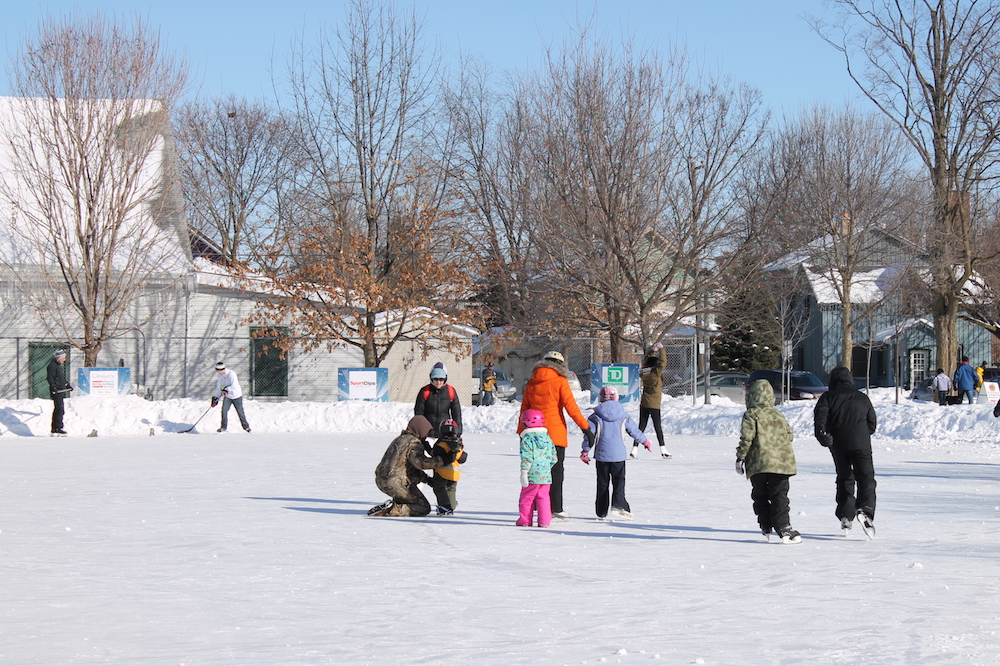 A colour image taken during the winter months that shows adults and children skating on a large outdoor rink. A couple of male skaters are holding hockey sticks. In the background to the left is a chain link fence with a large white building directly behind it, to the right two houses are visible.