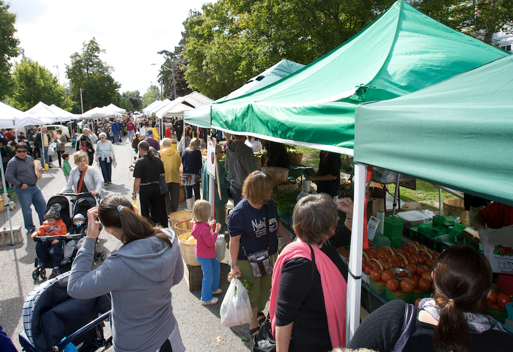 A colour photograph of a contemporary outdoor farmers' market that has two rows of tall portable canopy tents that are running parallel to one another with a crowd of people walking between them. Underneath the tents are vendors who are selling produce and other items that aren't clear.