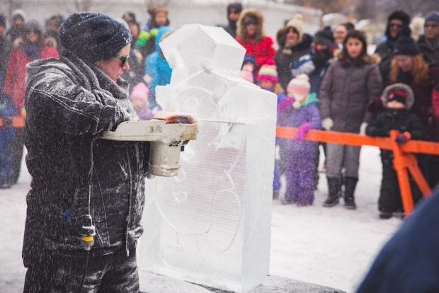 A colour image taken during the winter months showing a woman who is using a chainsaw to carve a snowman figure out a large block of ice. The background is out of focus but a crowd of adult and youth onlookers who are dressed in winter attire and gathered behind a bright orange barricade is visible.