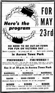 A black and white newspaper advertisement for Victoria Day featuring a graphic image of a large firecracker in the upper left corner and descriptive text about the event.