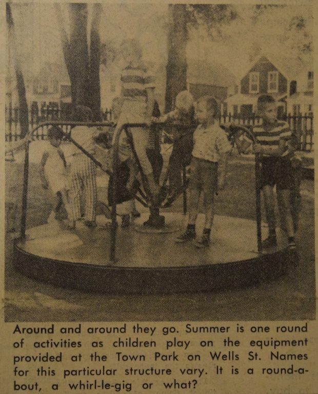 A sepia, black and grey image of nine children playing on a merry go round in an outdoor park. In the background is a picket fence and houses. There is a small caption in black text underneath the image.