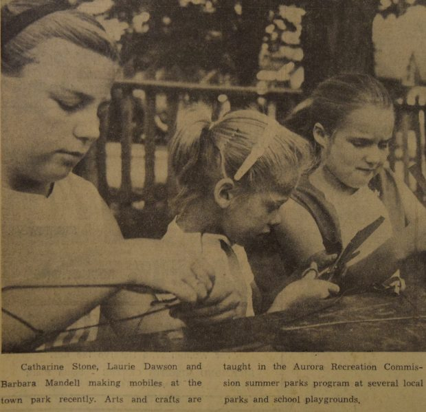 A sepia and black image of three girls who are working at an outdoor table on individual craft projects. There is a small caption in black text underneath the image.