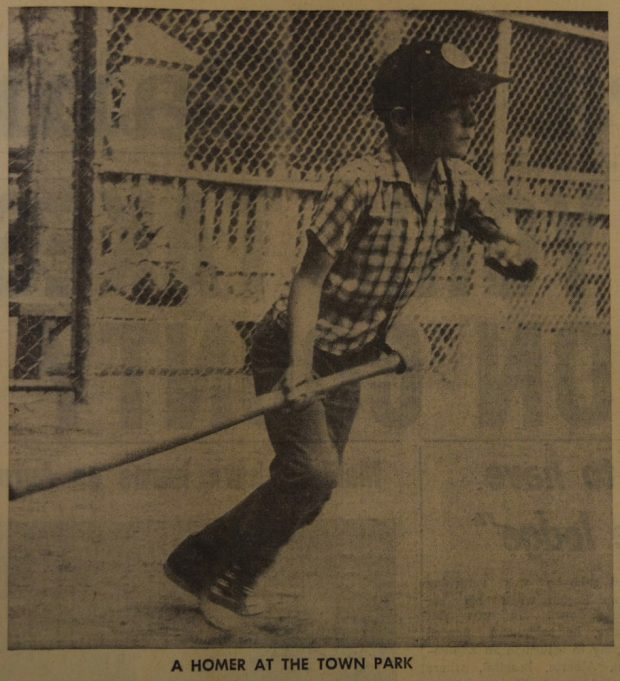 A sepia and black image of a young boy playing baseball outside. He is holding a baseball bat and appears to have just finished swinging it. The boy is staring off into the distance and looks like he is about to start running. In the background a tall chain link fence is visible as well as a shorter wooden picket fence behind it. There is a small caption in black text underneath the image.