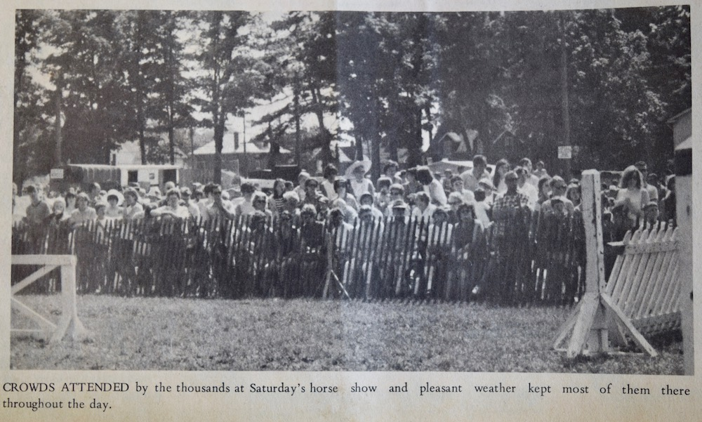 A black and white image taken in a park with a large crowd gathered in the distance behind a wooden picket fence. Behind the crowd are mature trees and houses. In the foreground pieces of white wooden structures are seen on both the left and the right side of the image. There is a caption of black text located directly below the image.