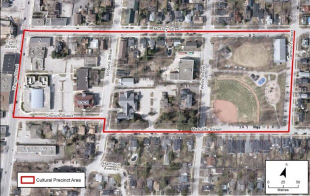 A colour aerial photograph of three blocks in Aurora known as the Cultural Precinct outlined in red; streets are labelled and directional and distance scales included in lower right corner