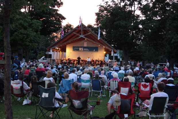 Colour photograph of a group of people seated on chairs in front of a band performing on a covered band shell in a park at dusk