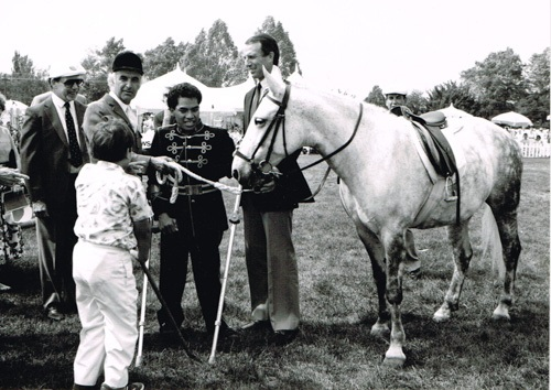 A black and white photograph of five people and a horse standing in a park setting; trees and tents visible in the background