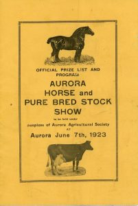 The front cover of a small rectangular program consisting of black lettering printed on a gold background with engraved illustrations of a horse and a cow all enclosed within a printed rectangular border
