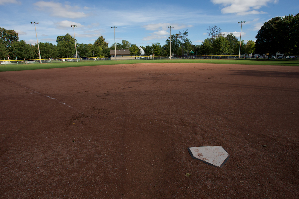 A colour image taken from behind home plate in a baseball diamond. The majority of the image shows the red dirt of the ball diamond and behind it is the grass of the outfield with a fence bordering it. In the background there is a row of mature trees and a small building close to the center of the image.