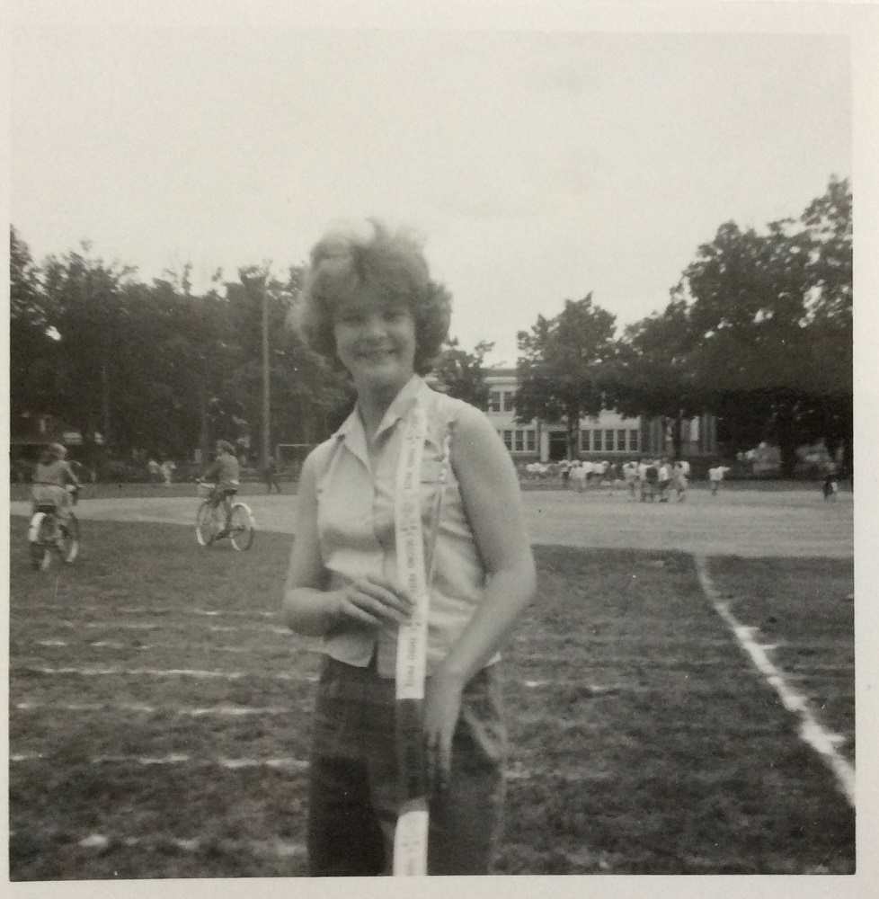 Black and white image of a girl standing in a large field with chalk lines on the grass. She is in the centre of the photograph and has a banner of track and field ribbons draped over her right shoulder. In the background on the left side there is a man and a woman each riding a bike across the field, on the right side is a group of kids playing in a crowd. A two-storey school house is also visiable in the background surrounded by mature trees.