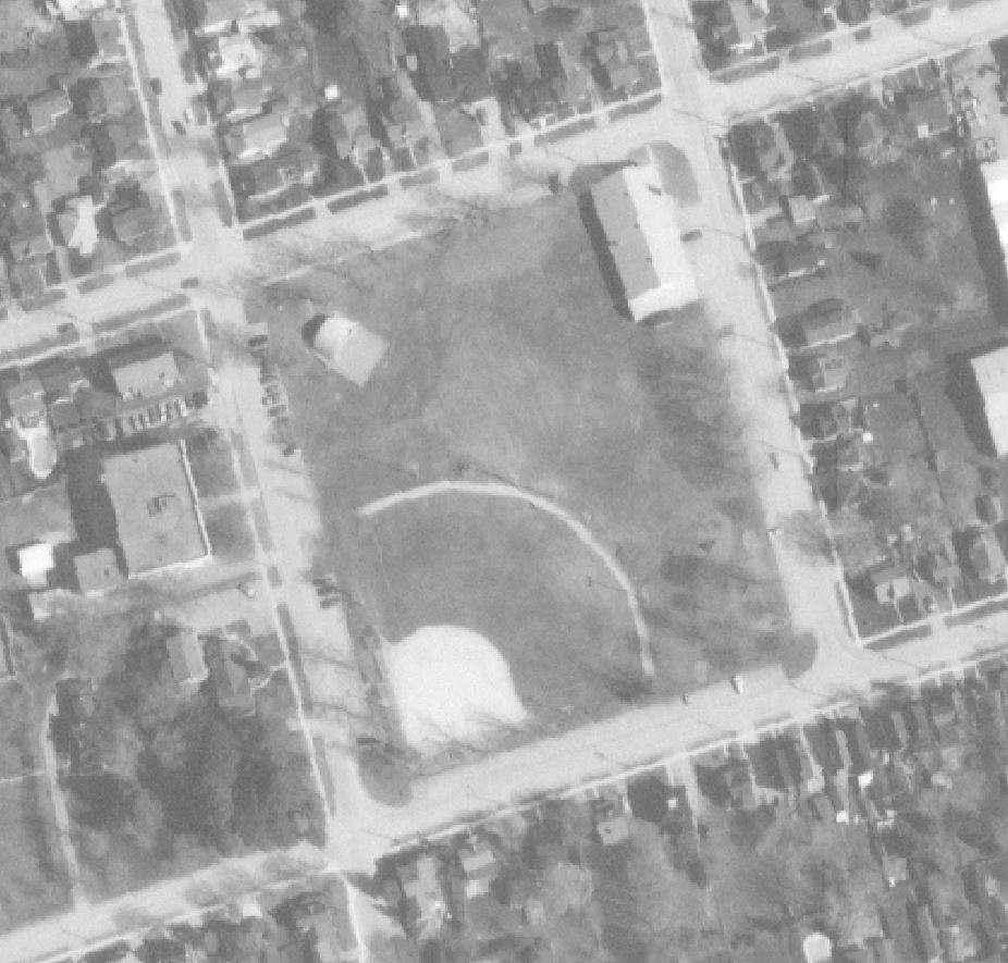 A black and white aerial photograph of Town park showing a ball diamond, band shell and Armoury building; adjacent streets and houses also visible in shot