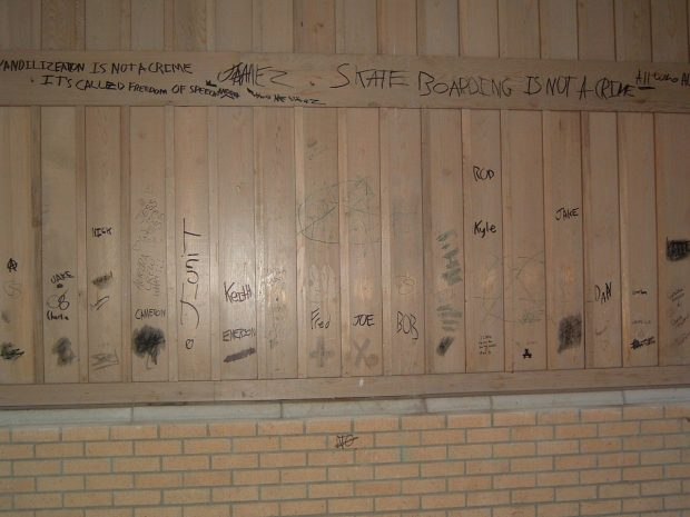 A photograph of a wooden and brick wall with graffiti written across in black ink