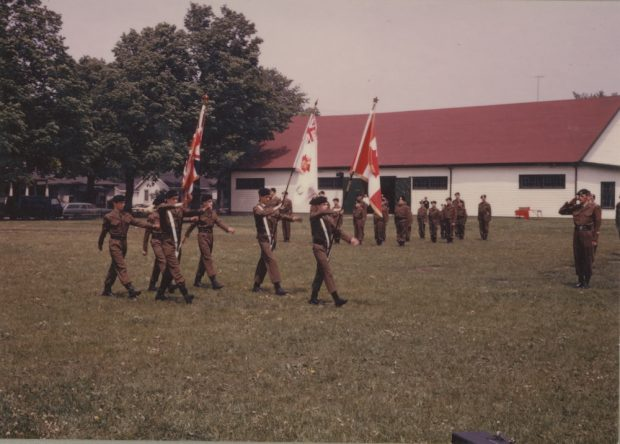 A colour photograph depicting uniformed boys parading with flags in a park setting; trees and a rectangular white clad building with red roof in the background