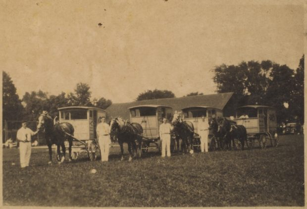 A sepia coloured image from c. 1930s showing four men dressed all in white standing in a park. To the right of each of them is a horse attached to a buggy. The man on the left side appears to be holding something in his hand. There is a fifth man seated inside of the buggy on the far right. In the background, a large roof and tall baseball diamond fence is visible.