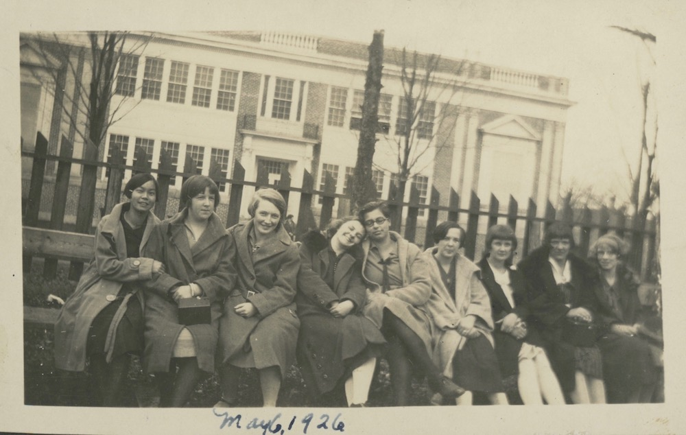 a sepia coloured photograph from 1926 showing nine girls seated on a bench with a wooden fence immediately behind them. A large two storey structure takes up the majority of the background. The image was taken on an angle so the fence and building appear to be slanted towards the right side.