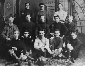 Formal black and white portrait taken inside of a photo studio featuring a football (soccer) team with three rows of men: the back row has three men standing, the middle row has five men seated on chairs, and the bottom row has five men seated on the floor. In front of the bottom row is a round ball that has 1896 written on it.
