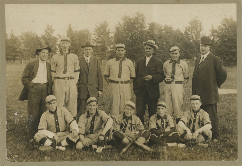 A sepia image of seven men standing and five sitting in front of them posing for a team photo. They are in a park and eight of the men are wearing a uniform.