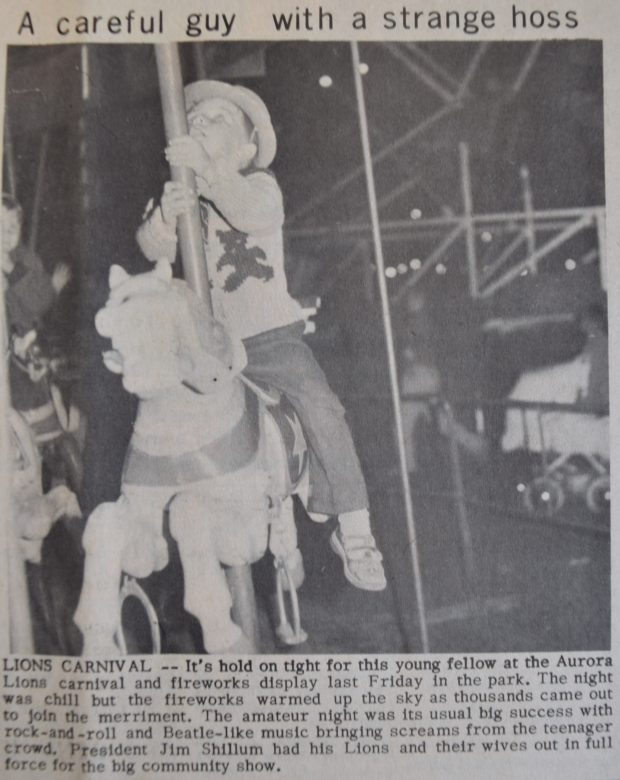 A black and white clipping from a newspaper depicting a photograph of a small boy on a merry-go-round horse; the young boy wears a hat and is looking up; a baby carriage, people and a ferris wheel are visible in the background.