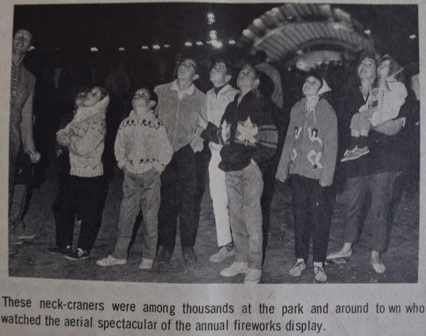 A black and white newspaper clipping showing a photograph of a group of people looking up into the night sky; lighted stage in background; typed text underneath