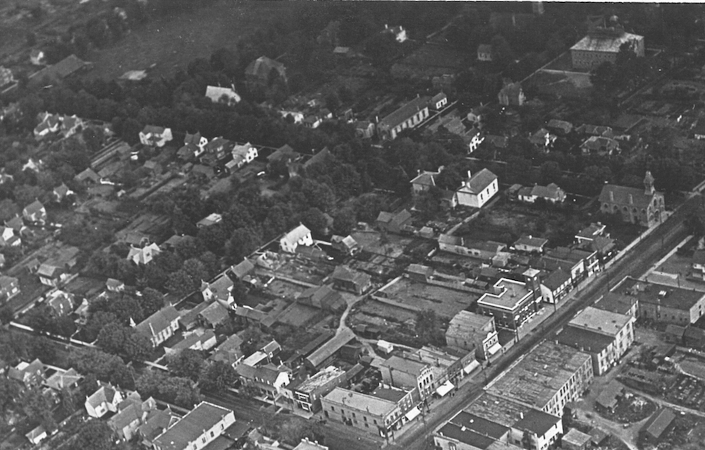 A black and white aerial image showing six blocks of a town. A variety of public and residential buildings can be seen as well as a park in the top left hand corner.