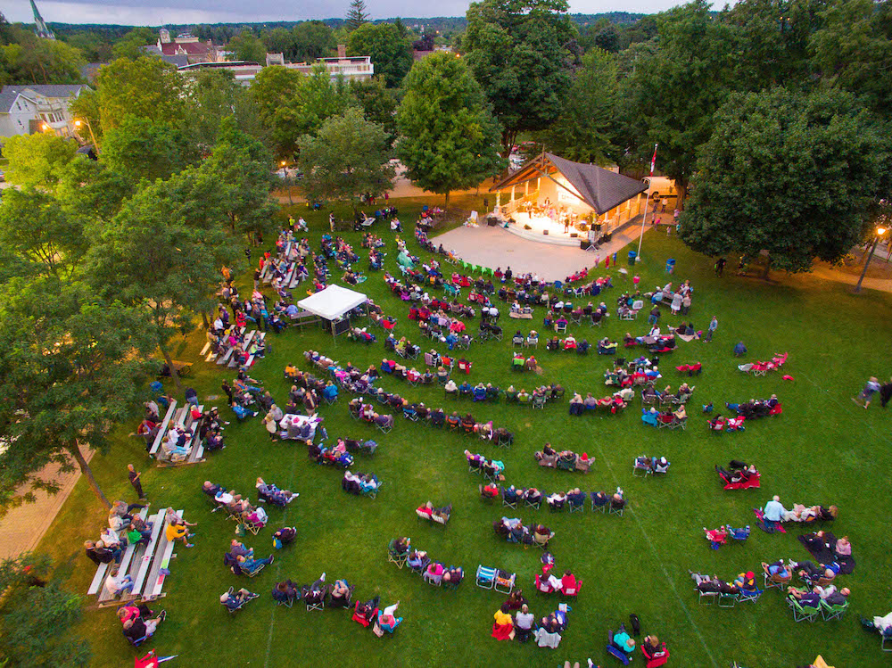 A colour photograph taken by a drone that gives a bird eye view of a section of a park that is bordered by mature trees. In the park people are seated, in no particular order, on a vast green lawn and are facing a covered performance stage that is brightly lit with musicians performing from it.