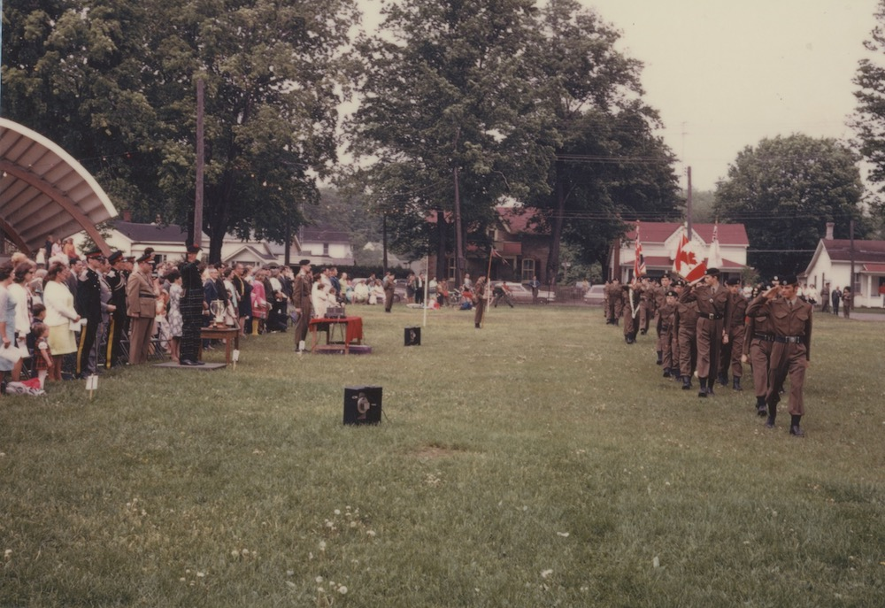 A colour image with a row of cadets marching in a park. They are close to the right hand side of the photo and are marching in the direction of the person taking the photo. On the left hand side of the image there is a crowd of onlookers who are watching the cadets and the roof of a bandshell is visible behind them. In the background some houses are visible as well as mature trees.