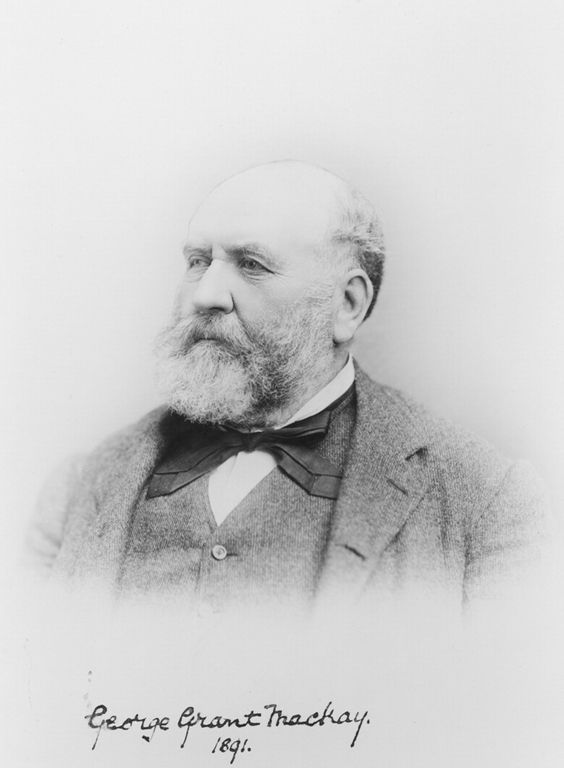 Black and white portrait of an older bearded man, dressed in a suit with a big bow tie.