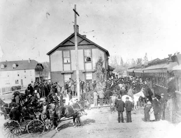 Black and white photo of a large crowd of well-dressed people at two-storey train station with a stationary train on the right. In the crowd, there are horses and carriages.