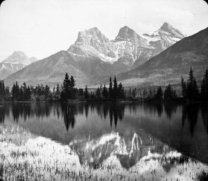 Black and white photo of three snow-covered dramatic peaks with a mirrored lake in front.