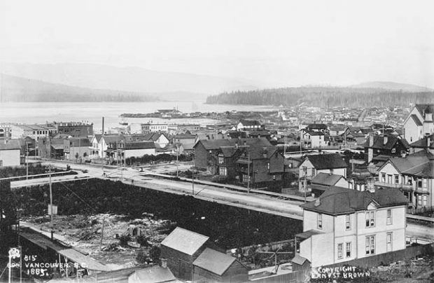 Black and white photo of a young coastal city with the ocean and mountains in the background. Early one and two storey buildings, a large empty lot and roads are in the foreground.
