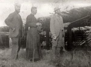 Black and white photo of three men outside. Two are in suits and the man to the right is pointing a walking stick. The man in the centre is wearing a cassock and holding a hat.