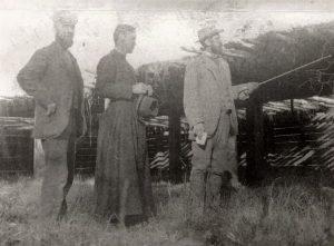 Photo en noir et blanc de trois hommes à l'extérieur. Deux d'entre eux portent un costume et l'homme de droite pointe une canne. L'homme au centre porte une soutane et tient un chapeau.