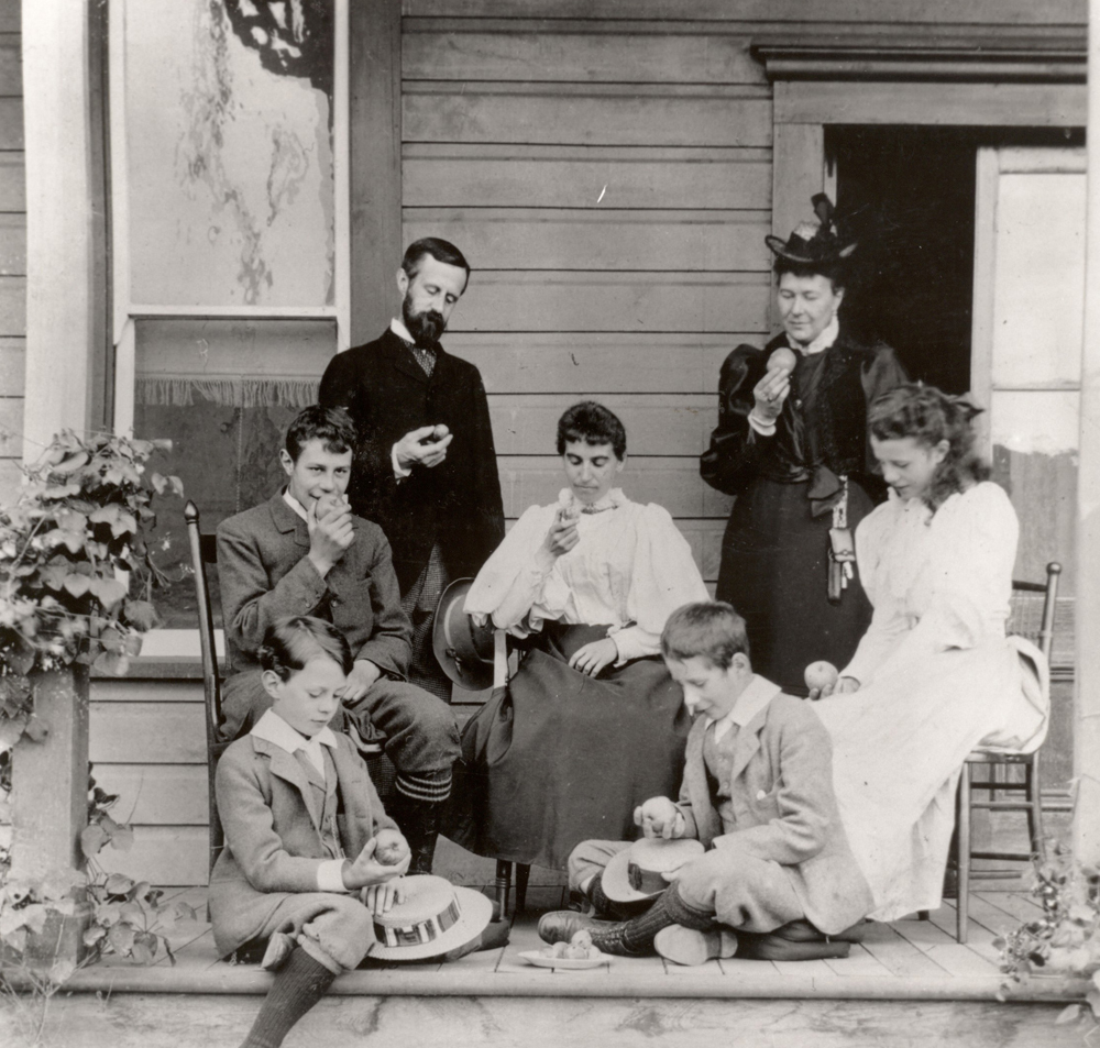 Black and white photo of a family sitting on a verandah. One man, two women, one girl, and three boys each looking at an apple in their hand.
