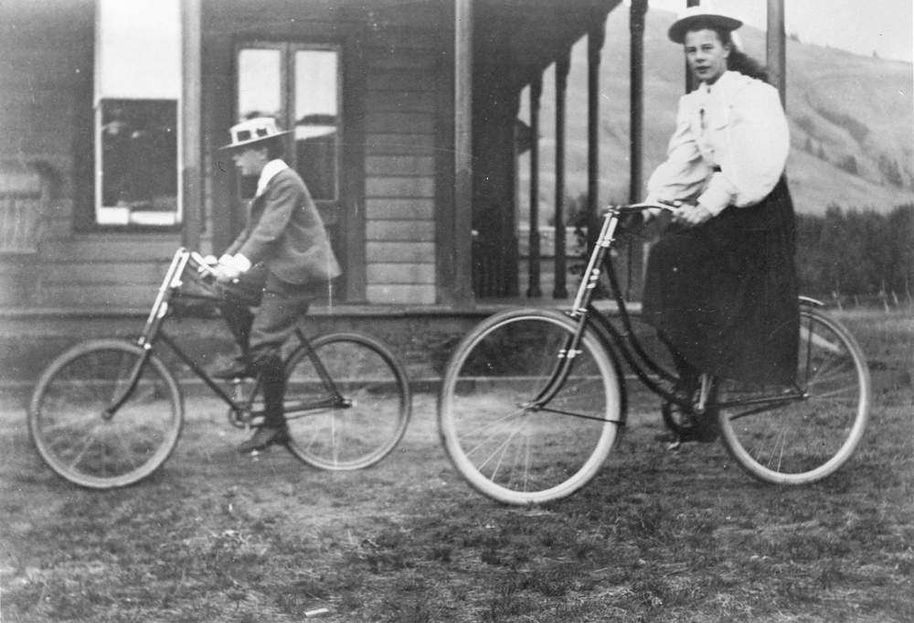 Black and white photo of a girl and a young boy riding bicycles near a house.