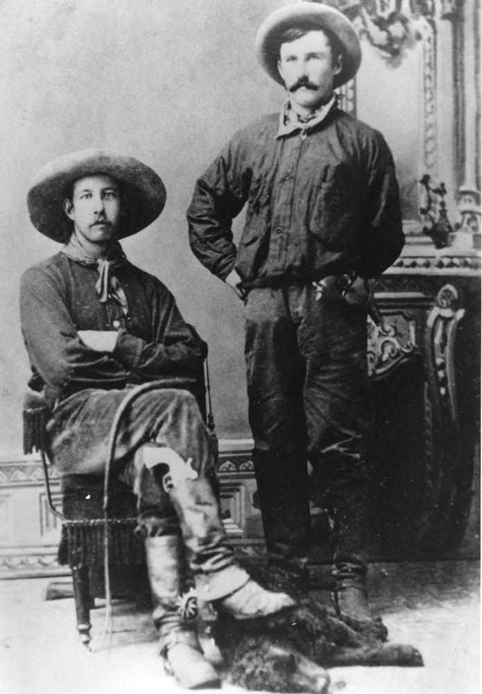 Black and white photo of two men in cowboy clothes and hats. One seated, one standing.