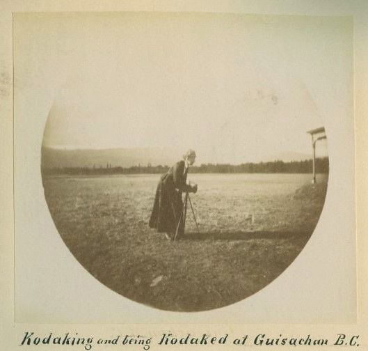 Faded sepia round photo of a woman in a field with an old-fashioned camera on a tripod.
