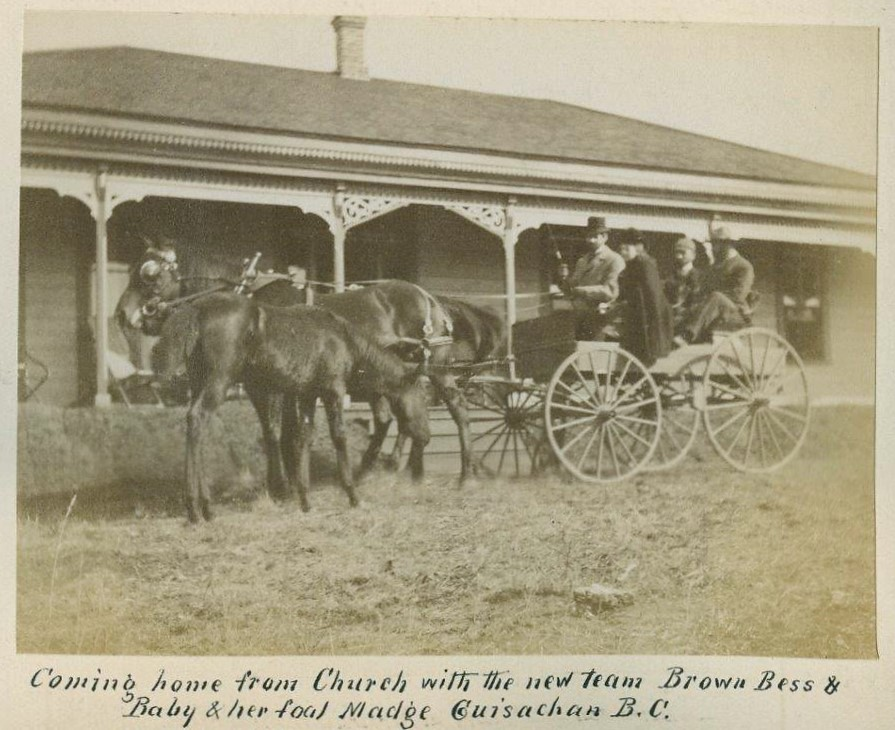 Black and white photo of a horse and wagon with four people in front of a house.