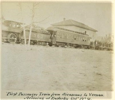 Black and white photo of a train, engine with passenger car and a building behind.