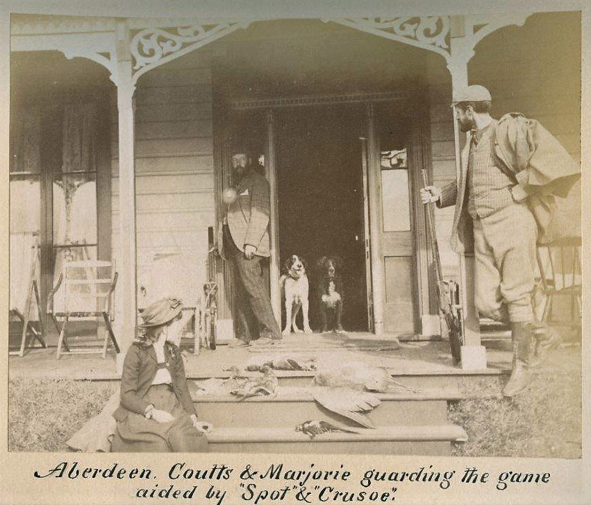 Black and white photo of two men, a girl, two dogs and dead birds on a porch. The man on the right is holding a rifle.