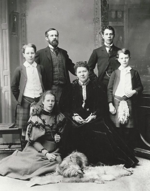 Black and white formal photo of a Victorian era family, a man, a woman, four children and a dog. Two of the boys are in kilts.