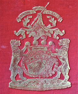 Silver family crest on a red background of two lions flanking shields with the motto