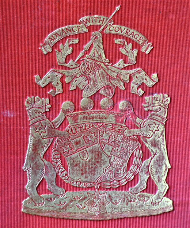 Silver family crest on a red background of two lions flanking shields with the motto Advance With Courage above.