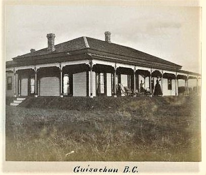 Black and white photo of the front and side of a one-storey house with a wrap-around verandah. A woman is standing on the verandah waving.