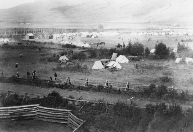 Black and white photo of fencing, white tents, one house, several small buildings, people and horses in a valley.